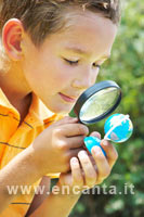 Immagine - un bambino che guarda un piccolo mappamondo attraverso una
